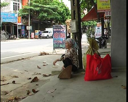 Bà đợi xe khách đi đến với những đứa trẻ ở thôn Đồng Tha