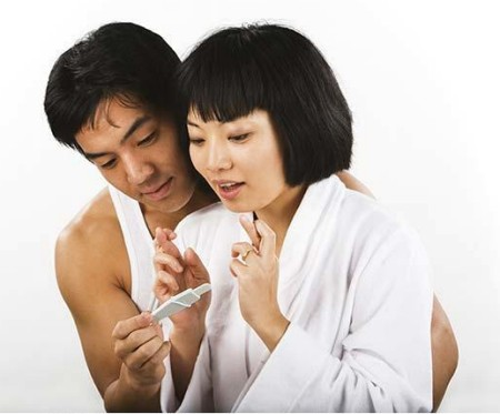Asian couple crossing fingers and looking at pregnancy test