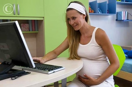 Pregnant woman sitting in front of a computer