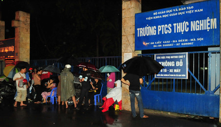 Từ 22h ngày 11/5 phụ huynh đã dầm mưa xếp hàng trước cổng trường để mua đơn vào lớp 1.