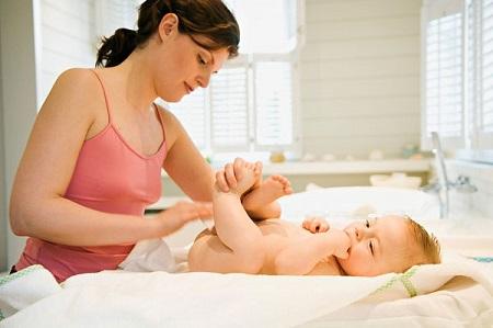 Thay tã mới sạch cho con, bắt đầu đặt từ dưới mông của bé.
