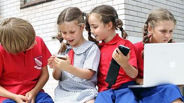 Bốn trẻ em từ 5 đến 8 tuổi tại một trường công ở Úc trong giờ chơi.