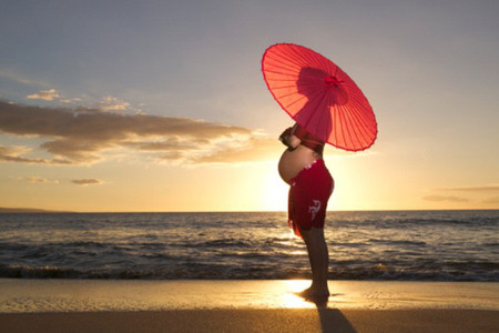 Pregnant woman on beach holding parasol