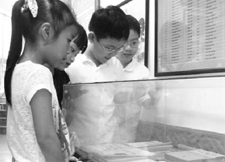 Học sinh Trường tiểu học Thăng Long (Hà Nội) đang tìm hiểu lịch sử tại phòng truyền thống nhà trường.